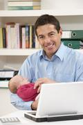 Father With Newborn Baby Working From Home Using Laptop Stock Photos