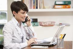 Woman Working From Home Using Laptop On Phone Stock Photos