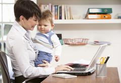 Woman With Baby Working From Home Using Laptop Stock Photos