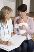 Mother With Newborn Baby Talking With Health Visitor At Home Stock Photos