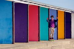 Boy On Skateboard Passing Coloured Walls Stock Photos