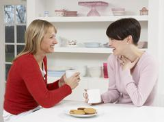 Two Women Enjoying Hot Drink In Kitchen Stock Photos