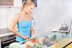 Woman in kitchen with laptop Stock Photos