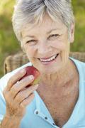 Senior woman eating apple - stock photo