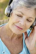 Senior woman with headphone - stock photo