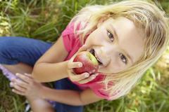 Portrait of happy girl with apple - stock photo