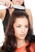 hairdresser combing woman's hair - stock photo