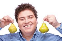Chubby boy and pear Stock Photos