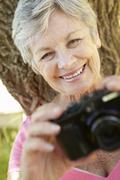 Senior woman with camera - stock photo