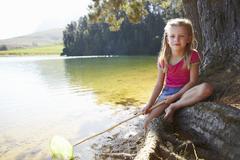Happy girl fishing at lake - stock photo