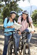 Senior couple with map on country bike ride - stock photo
