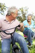Senior couple playing on children's bikes Stock Photos