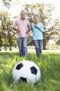 Vanhempi pari pelaa jalkapalloa Kuvituskuvat