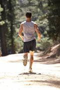 Stock Photo of Young man running along country lane