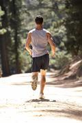 Young man running along country lane Stock Photos