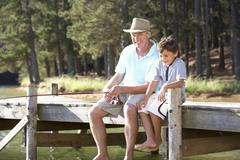 Senior man fishing with grandson Stock Photos