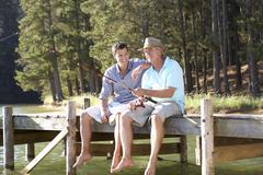 Father and adult son fishing together Stock Photos