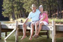 Senior couple sitting by lake Stock Photos