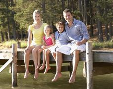Young family sitting by lake Stock Photos