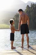 Father and son standing on jetty Stock Photos