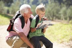 Senior man reading map with grandson on country walk Stock Photos