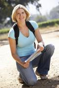 Woman with map on country walk - stock photo