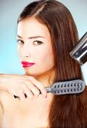 Woman holding blow dryer and comb Stock Photos