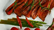 Curved meat slices on white dish with vegetables Stock Footage