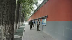 Chinese people walking under Beijing imperial red wall & read newspaper. Stock Footage