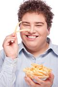 chubby man with french fries - stock photo