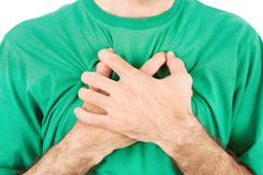 both man's hands on breast because of hard breathing - stock photo