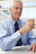 Senior businessman with laptop and coffee - stock photo