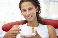 Young woman relaxing with cup of tea Stock Photos