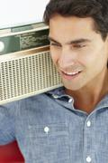 Young man listening to radio - stock photo