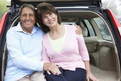Senior Hispanic couple outdoors with car - stock photo