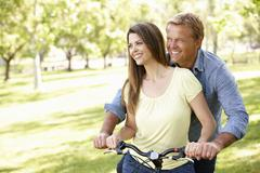 Couple with bike in park - stock photo