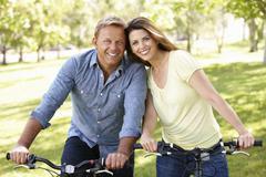 Couple riding bikes in park Stock Photos
