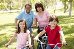 Hispanic family riding bikes in park Stock Photos