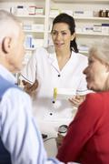 American pharmacist dispensing to senior couple Stock Photos