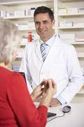 American pharmacist with senior woman in pharmacy - stock photo