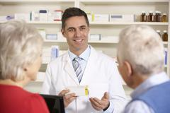 American pharmacist with senior couple in pharmacy - stock photo