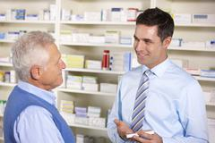 UK pharmacist serving  senior man in pharmacy - stock photo