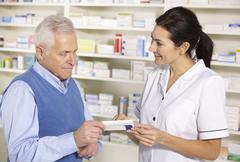 American pharmacist serving  senior man in pharmacy - stock photo