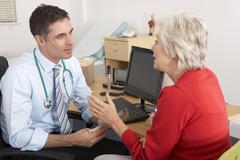 British GP talking to senior woman in surgery - stock photo