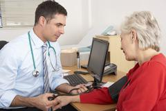British doctor taking senior woman's blood pressure - stock photo