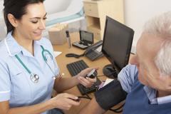 British nurse taking senior man's blood pressure - stock photo