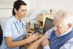 British nurse giving injection to senior man Stock Photos