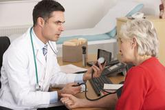 American doctor taking senior woman's blood pressure - stock photo
