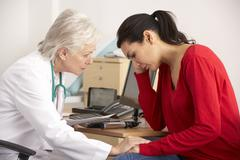 American doctor with depressed woman patient - stock photo