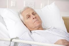 Senior man ill in hospital bed Stock Photos